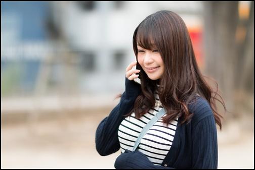 笑顔でスマホで電話する女性の画像