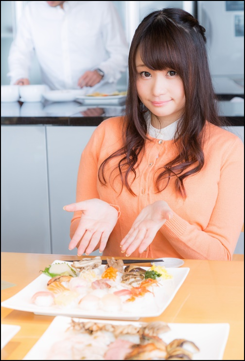 お寿司を紹介する女性の画像