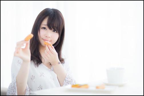 カメラ目線で食べるのポーズ女子の画像