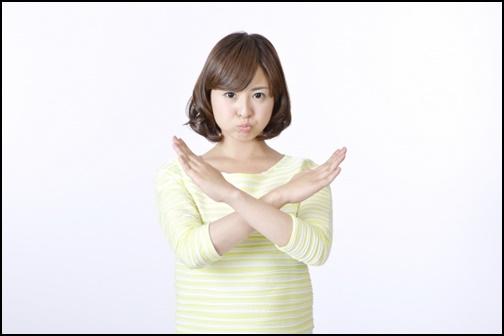 バツのポーズをする女性の画像