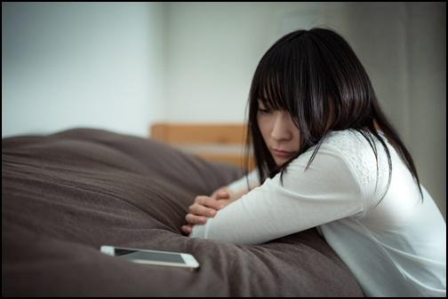 スマホを見て疲れている婚活女性の画像
