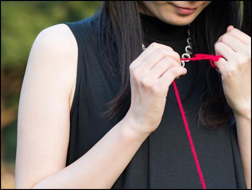 運命の赤い糸を眺める女性の画像
