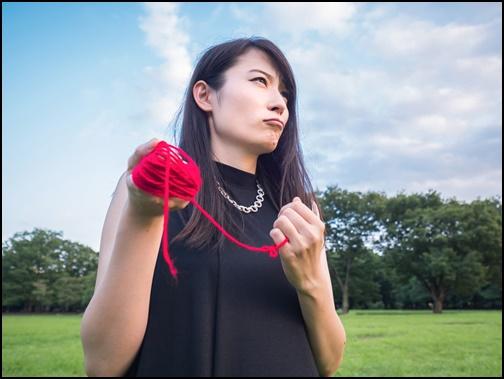 運命の赤い糸を探す女性の画像