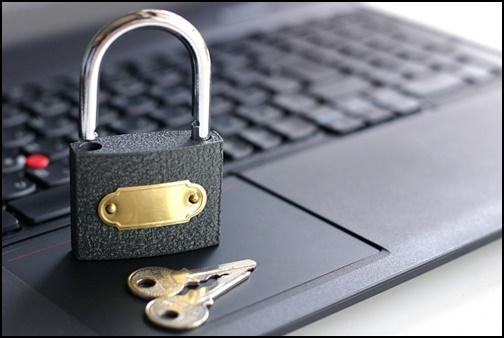ノートパソコンと鍵の画像