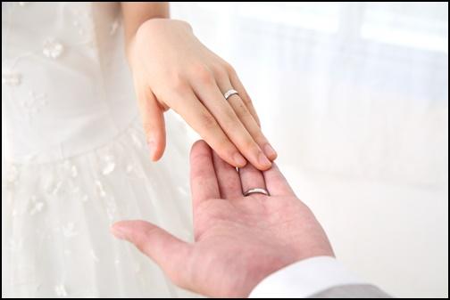 結婚指輪をつけ手を触れあうカップルの画像