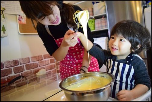 子供と母親が料理を作る画像