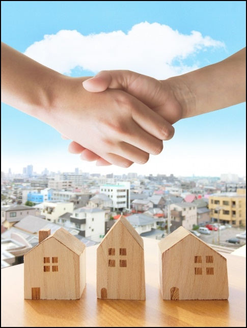 握手と模型の家が3個ある画像