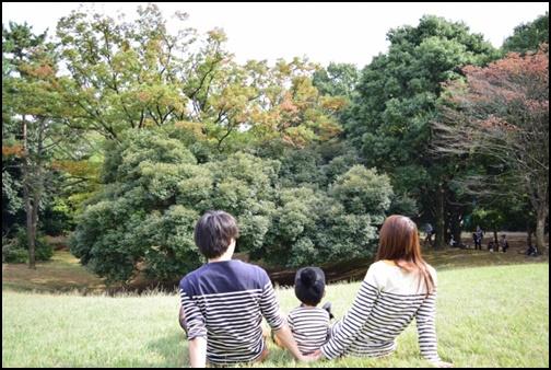 草原で座って手を繋ぎ合わせる親子の画像
