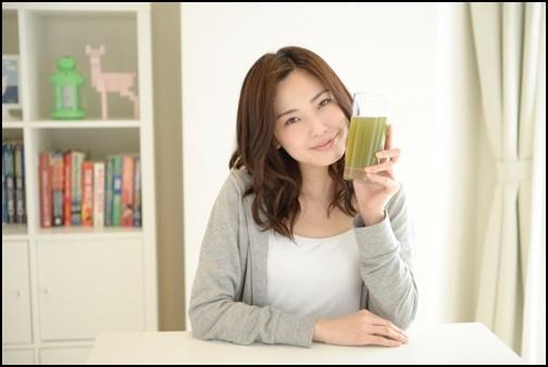 グリーンスムージを持つ女性の画像