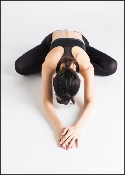 胡坐をかいて前屈する女性の画像