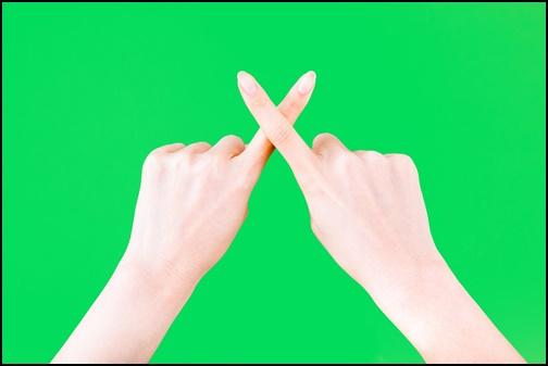指でバツのポーズをした画像
