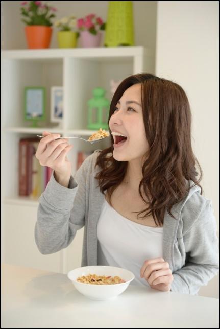 グラノーラを食べる女性の画像