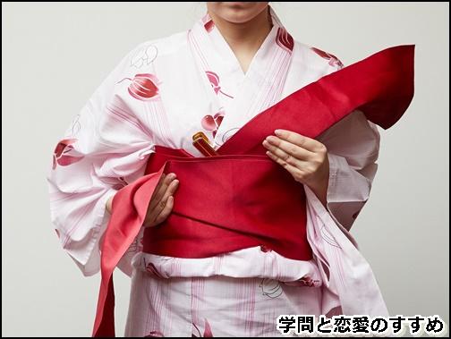 巻いてきた帯の下を内側に、斜めに織り上げて浴衣の帯を結ぼうとしている画像