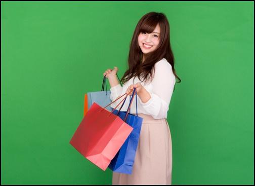 買い物袋を持って笑顔の女性画像