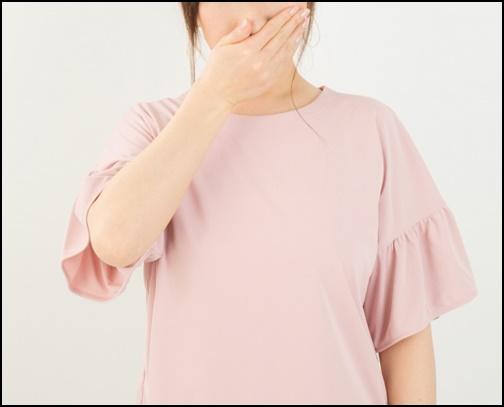 鼻を押さえる女性の画像