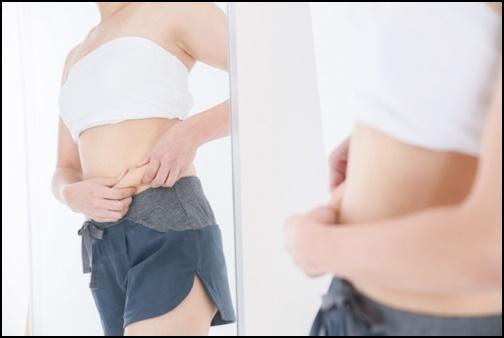 お腹の肉をつまむ女性の画像