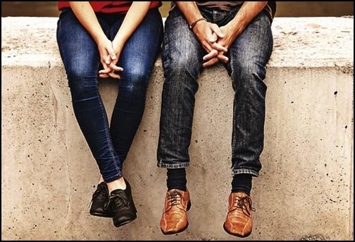 ジーンズ姿で座るカップル画像