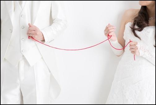 ウエディングドレス姿で赤い糸を繋げている画像