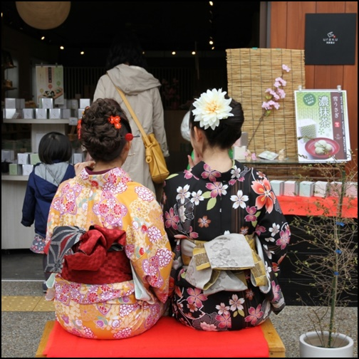 京都でレストラン前に座って待つ着物を来た女性の画像