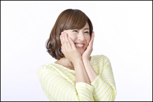 頬に手を当てて笑顔の女性の画像