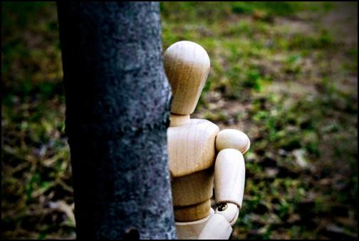 木の陰から見つめる木の人形画像