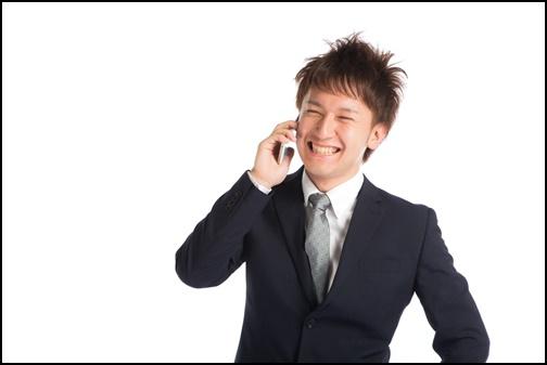 サラリーマン男性が電話を掛けている画像