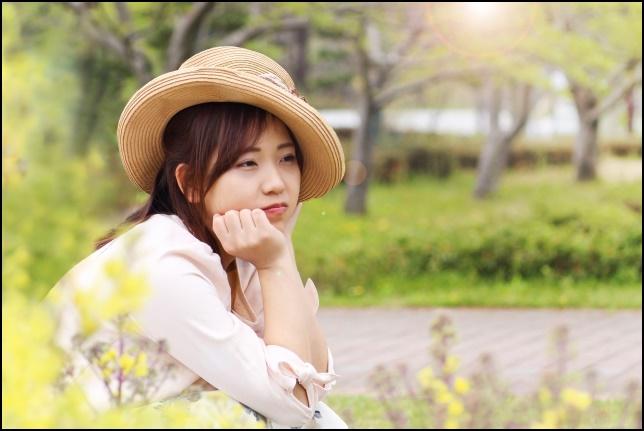 帽子をかぶって遠くを見つめる女性の画像