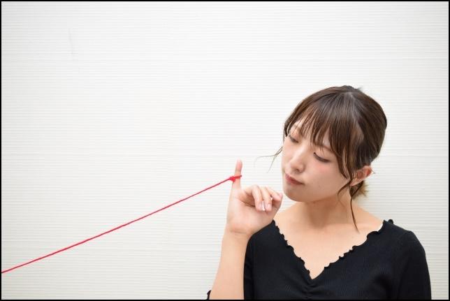 運命の赤い糸を見つめる女性の画像