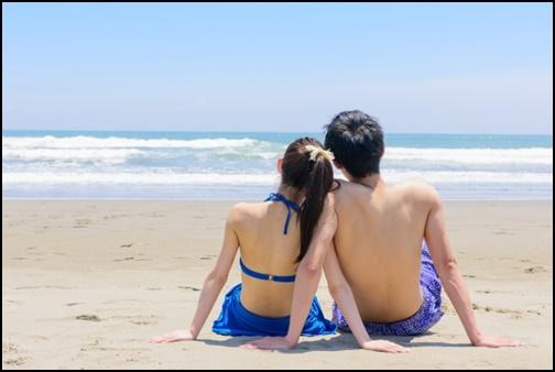 水着姿のカップルが浜辺で座っている画像