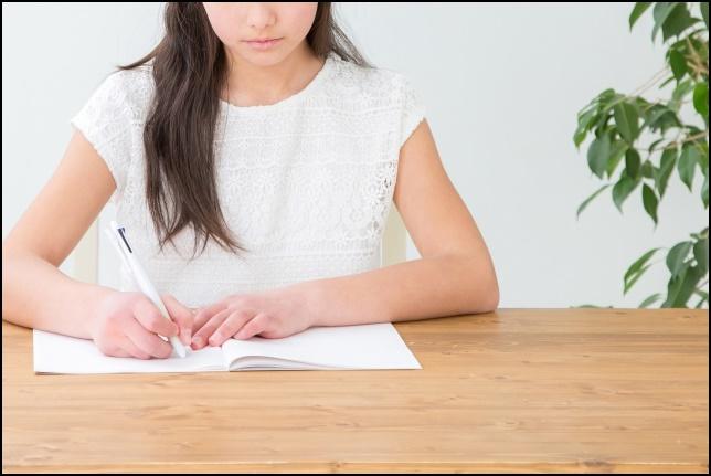 ノートにメモを取って勉強している女性の画像