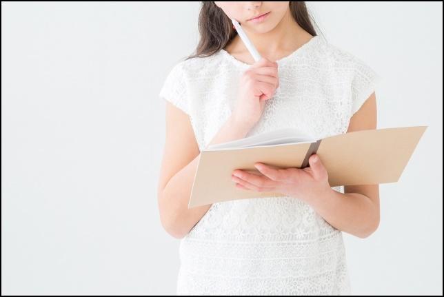 ノートを見て勉強しながら考えている女性の画像