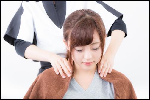 女性の肩もみマッサージをしている画像
