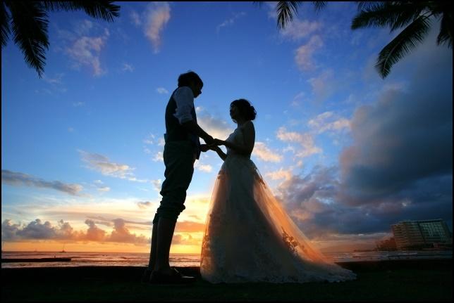 夕焼けをバックに結婚指輪を交換するカップル画像