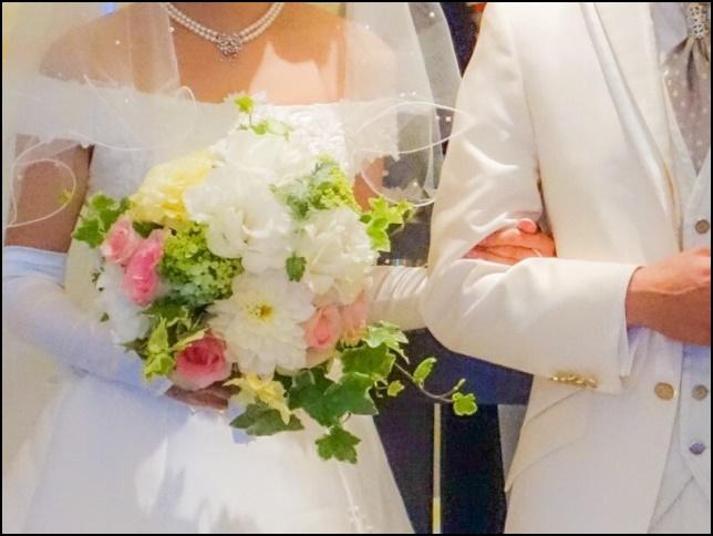 腕を組んで結婚式に向かうカップル画像
