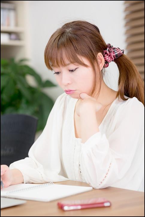 美人女性がメモを取って勉強している画像
