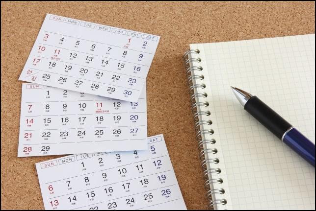 カレンダーとノートとボールペンの画像