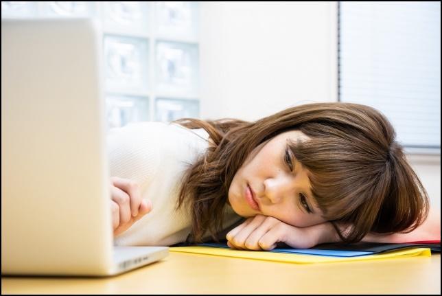 仕事に就かれて机で寝ている女性の画像