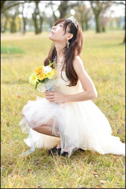 ウエディングドレスを着て座りながらブーケを持って上を見上げる美人女性の画像