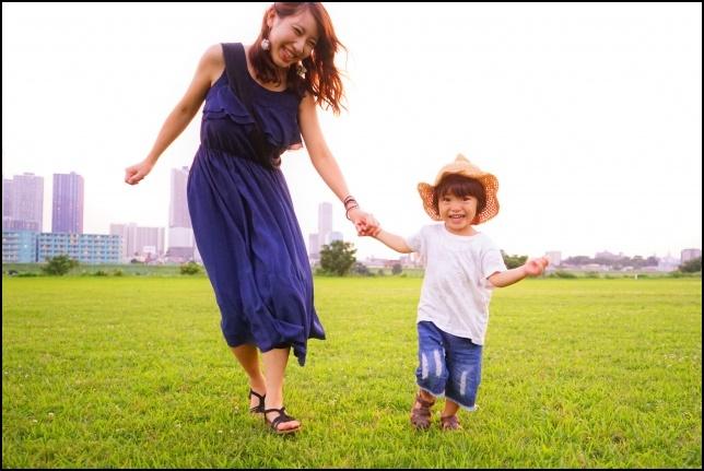 優しいお母さんと男の子が手をつないで公演を散歩している画像