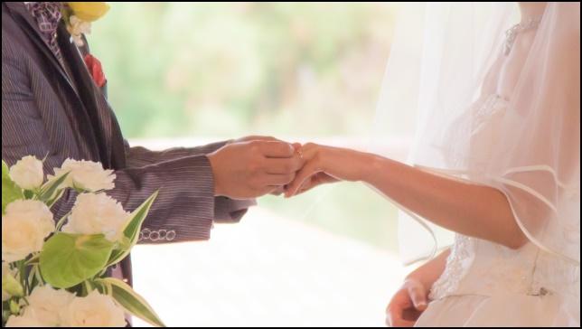 ウエディングドレスとスーツ男性の結婚指輪交換の画像