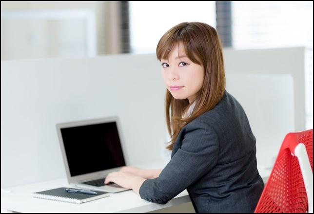 美人OLがパソコン入力中振り向いてこちらを向いている画像