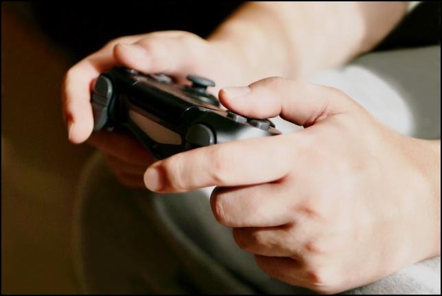 ゲームコントローラーを持つ手の画像