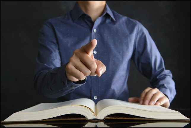 男性が書籍を開いて指差し説明している画像