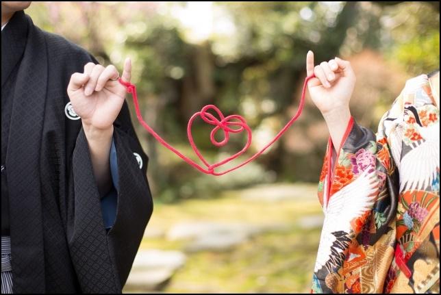 和服姿の結婚式みたいな場面で運命の赤い糸で繋がれている画像