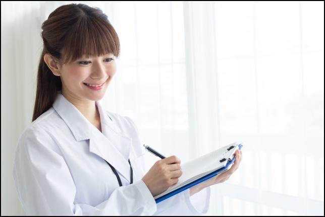 医者の女性がカルテを書いている画像