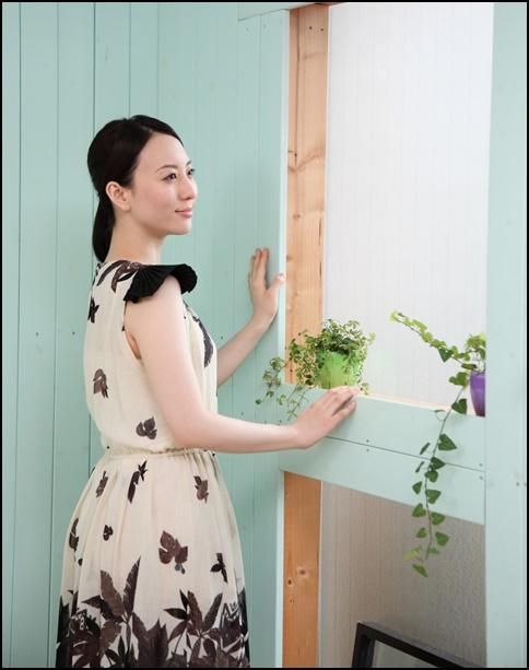 知的な女性が窓際で外を見ている画像