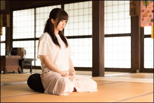 座禅して瞑想している女性を横から撮影した画像