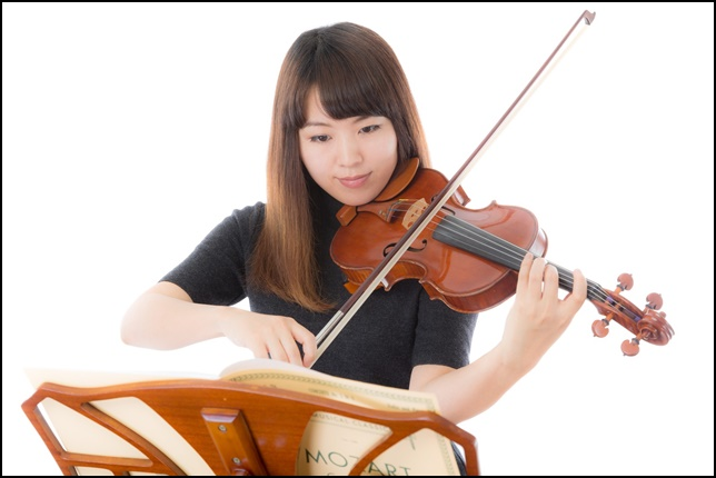 楽譜を見ながらヴァイオリン演奏をしている画像1